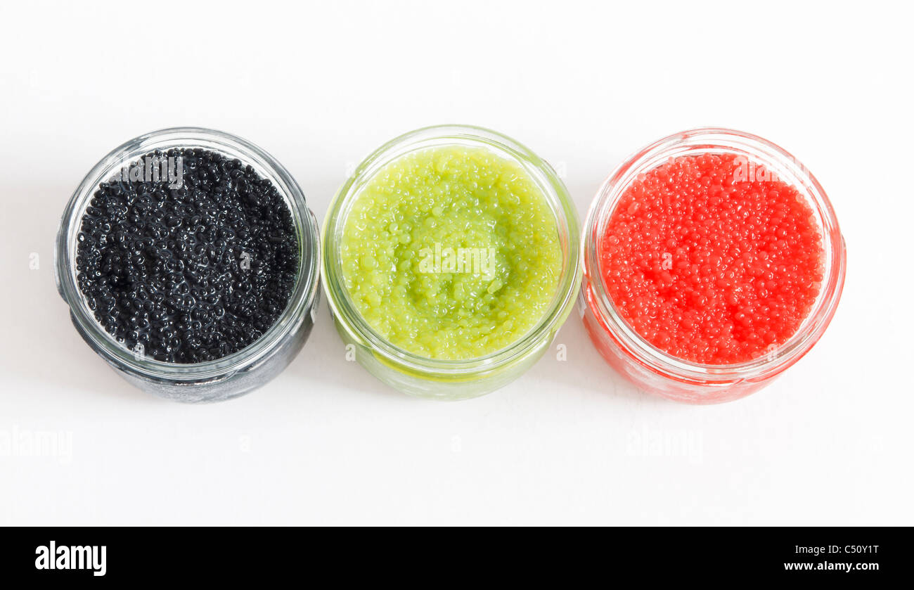 red, green and black caviar in glass jars on withe background - Stock Image