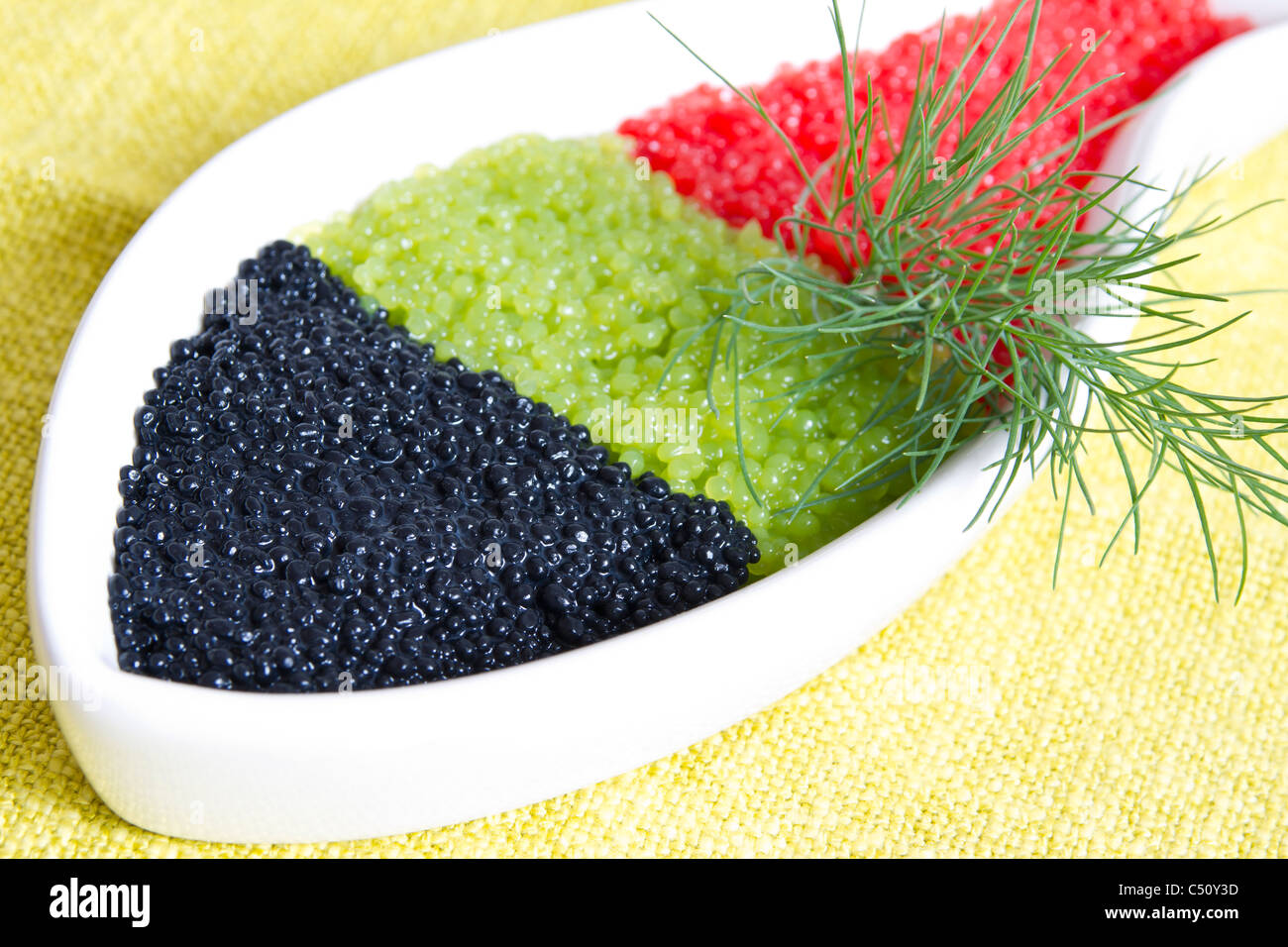 caviar in a bowl-shaped over on yellow background - Stock Image