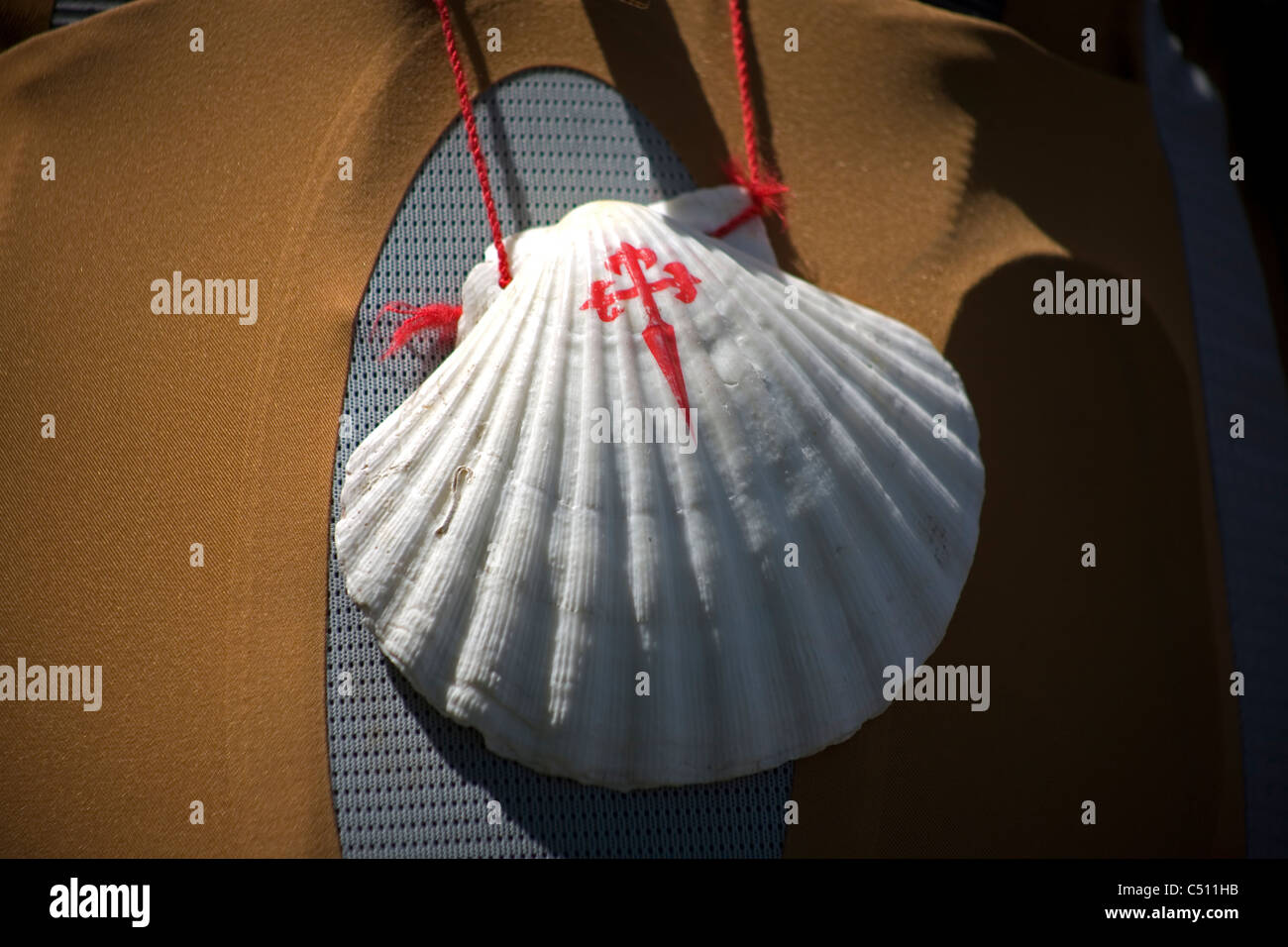 A scallop shell with the Cross of Saint James hangs in a backpack of a pilgrim walking in the French Way of St. - Stock Image