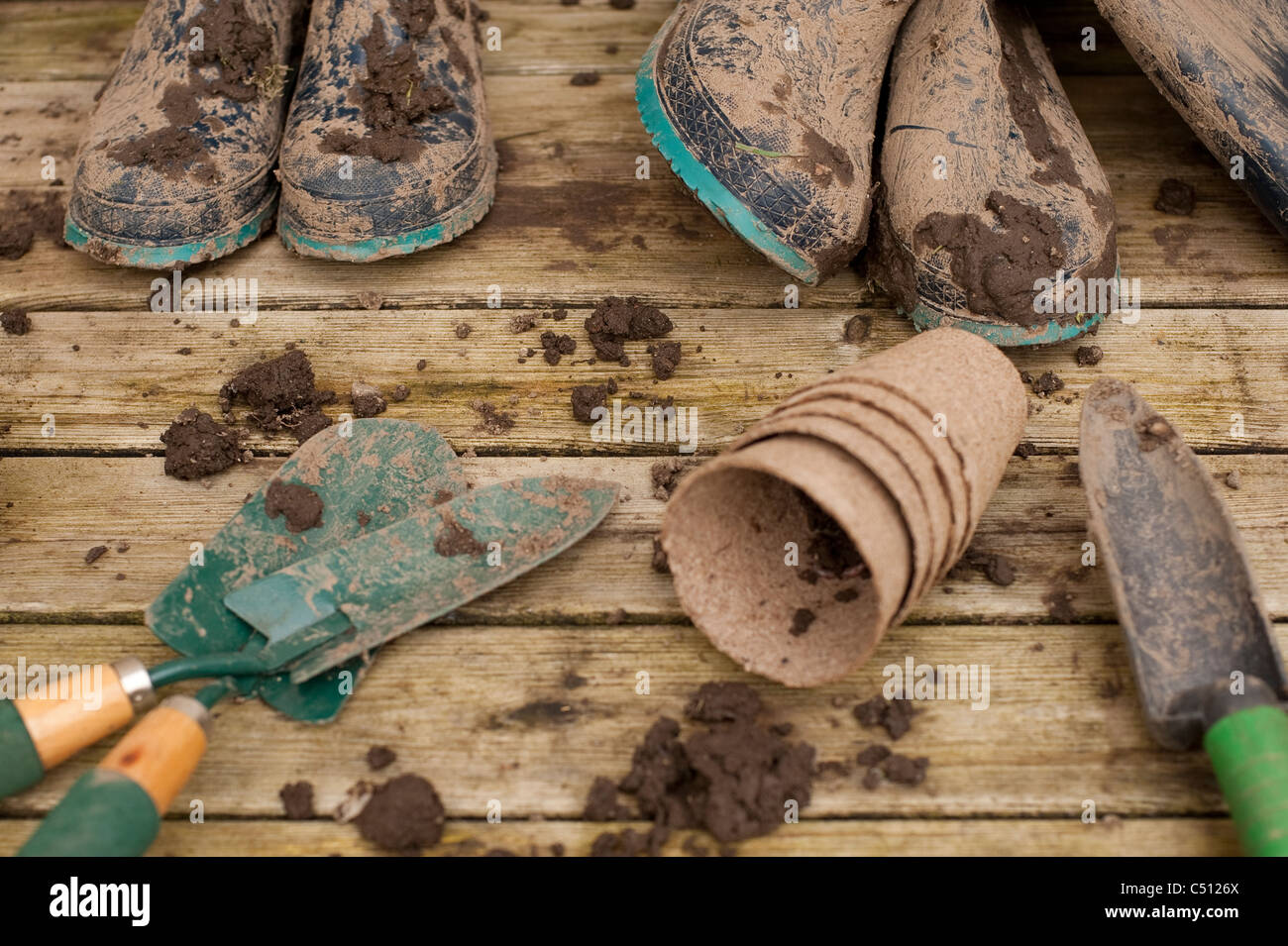 Muddy boots and gardening tools on back deck with flower pots with hyacinth bulb in pot after working in garden. Stock Photo