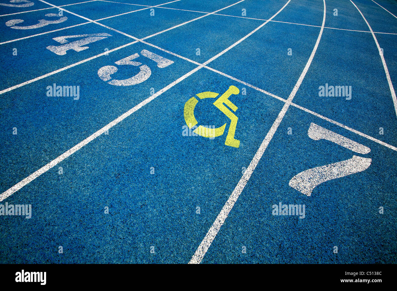 Handicap wheelchair icon superimposed on top of running track. Stock Photo
