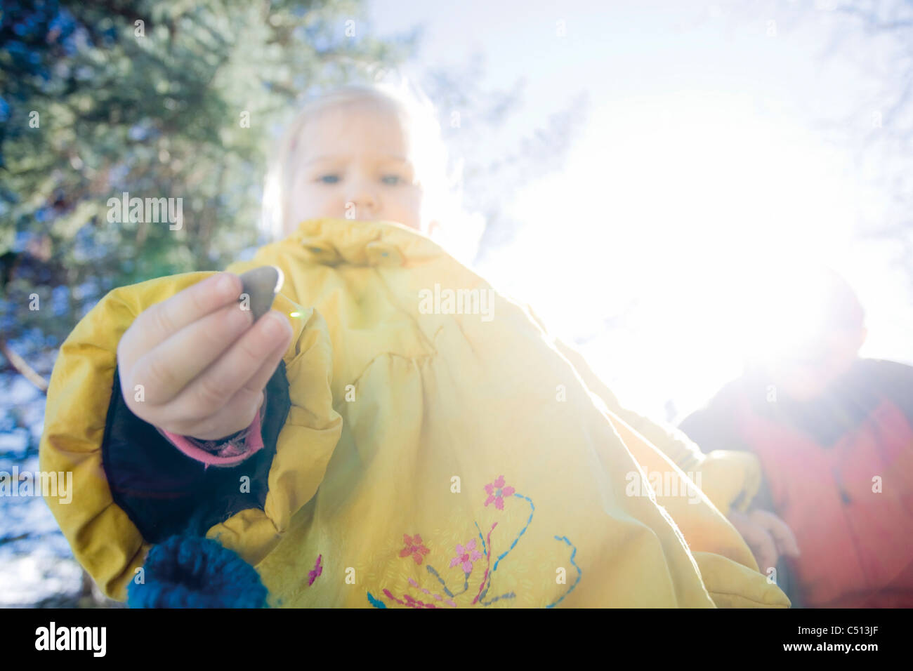 Baby girl looking at pebble in hand curiously, low angle view - Stock Image