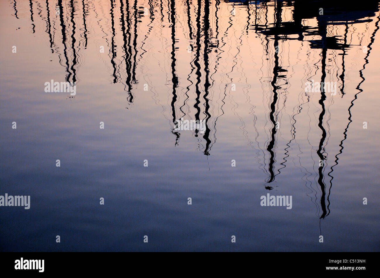 Silhouetted masts reflected on water at sunset - Stock Image