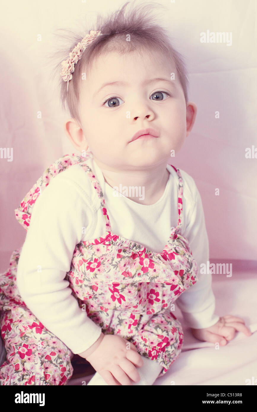 Baby girl in floral dress, portrait - Stock Image