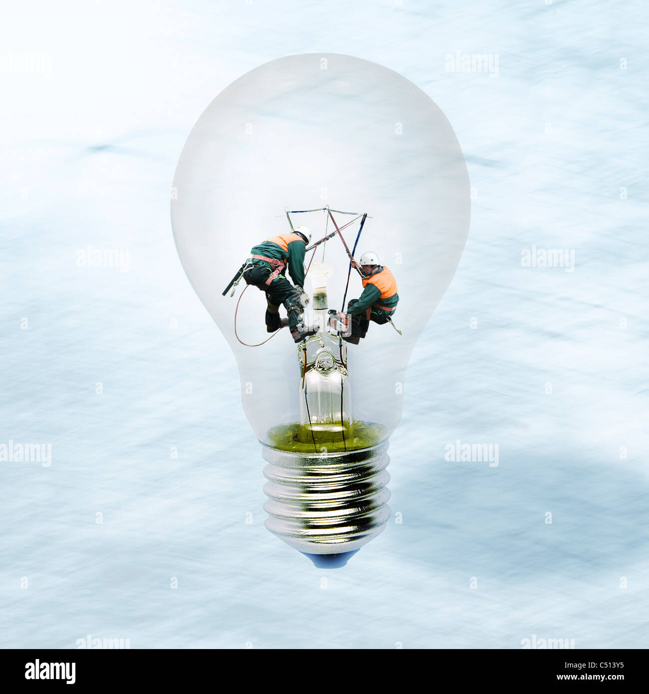 Linemen working inside of clear light bulb - Stock Image