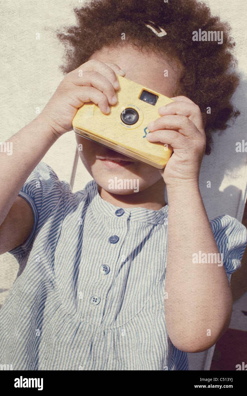 Little girl holding camera - Stock Image