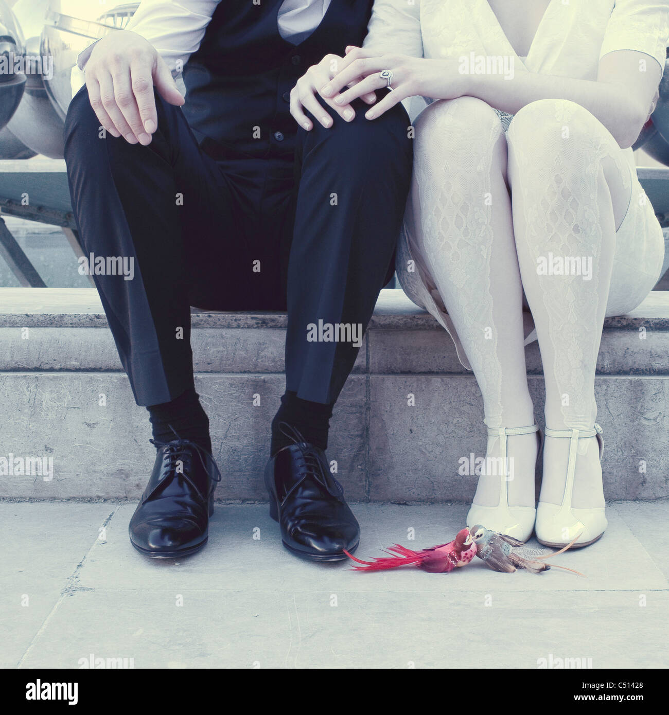 Couple sitting side by side, low section - Stock Image
