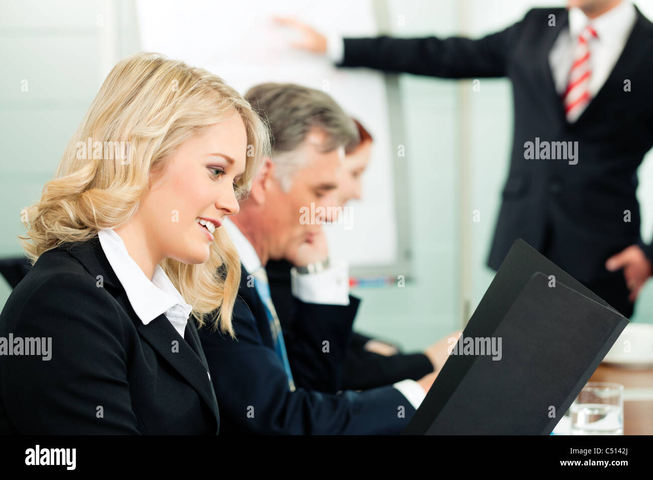 Business - presentation within a team; a colleague is standing on the flipchart - Stock Image