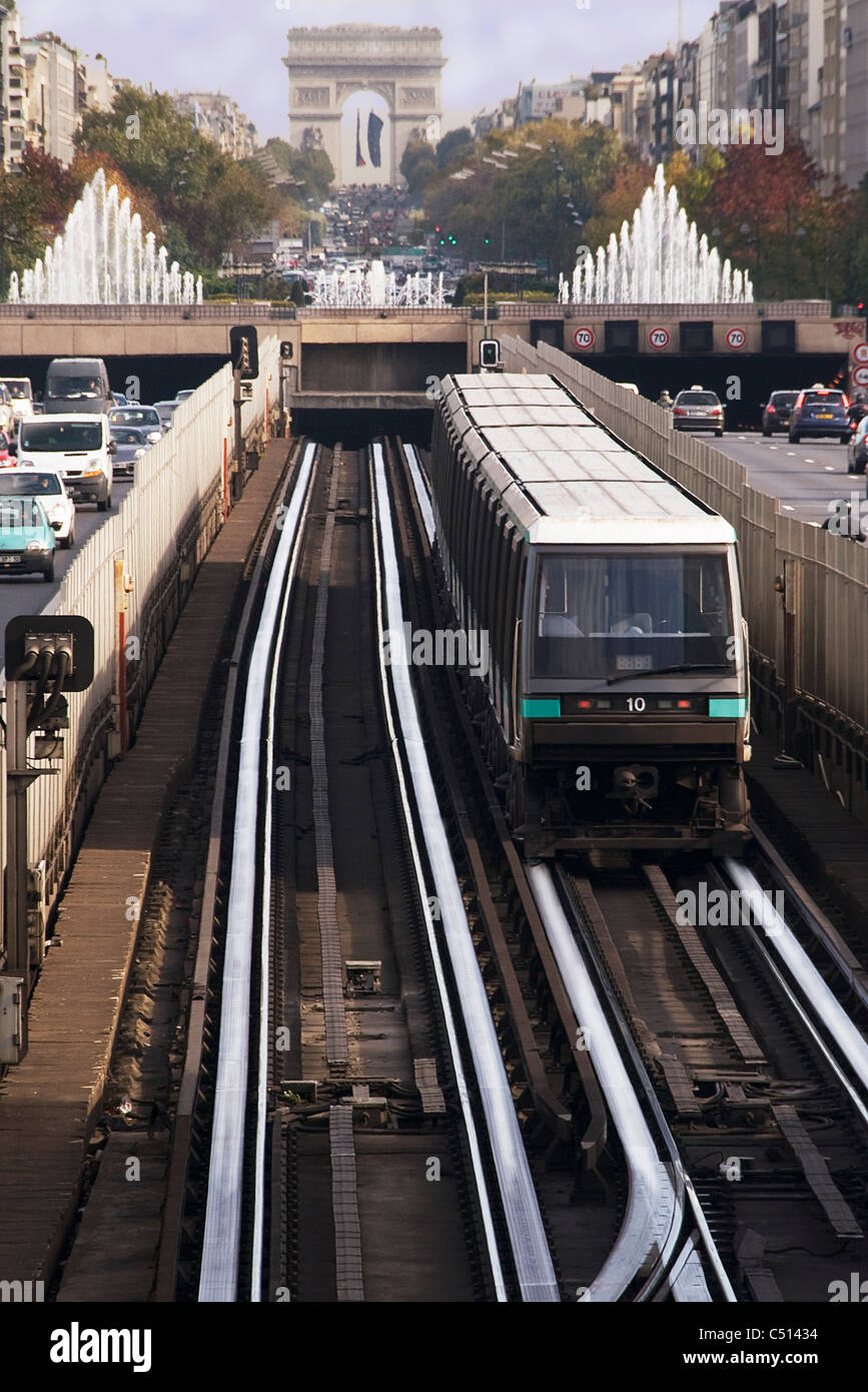 Subway train running on rail track in city, Arc de Triomphe in background - Stock Image