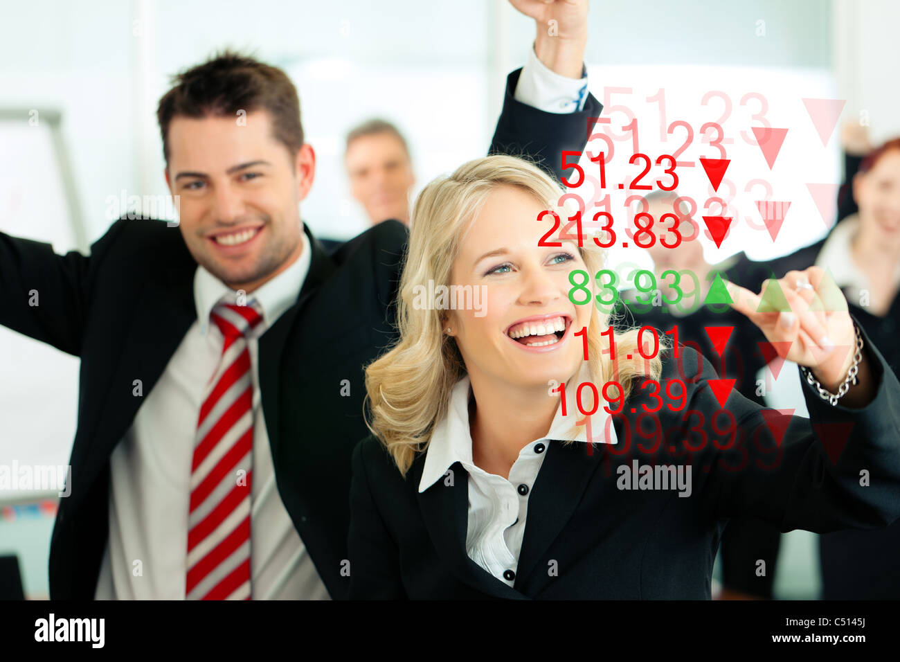 Business - presentation within a team; a female banker or consultant shows figures or share prices on screen - Stock Image