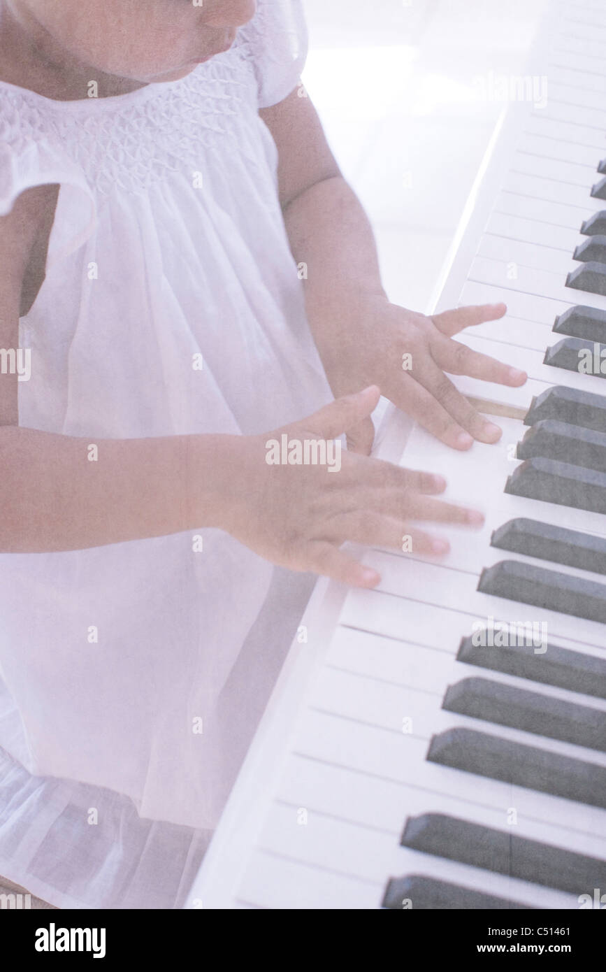 Little girl playing piano, cropped - Stock Image
