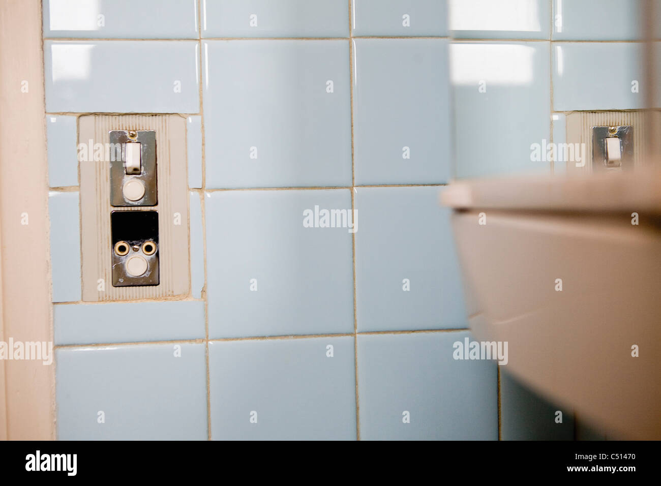 Ight switch and electrical outlet on tiled wall - Stock Image