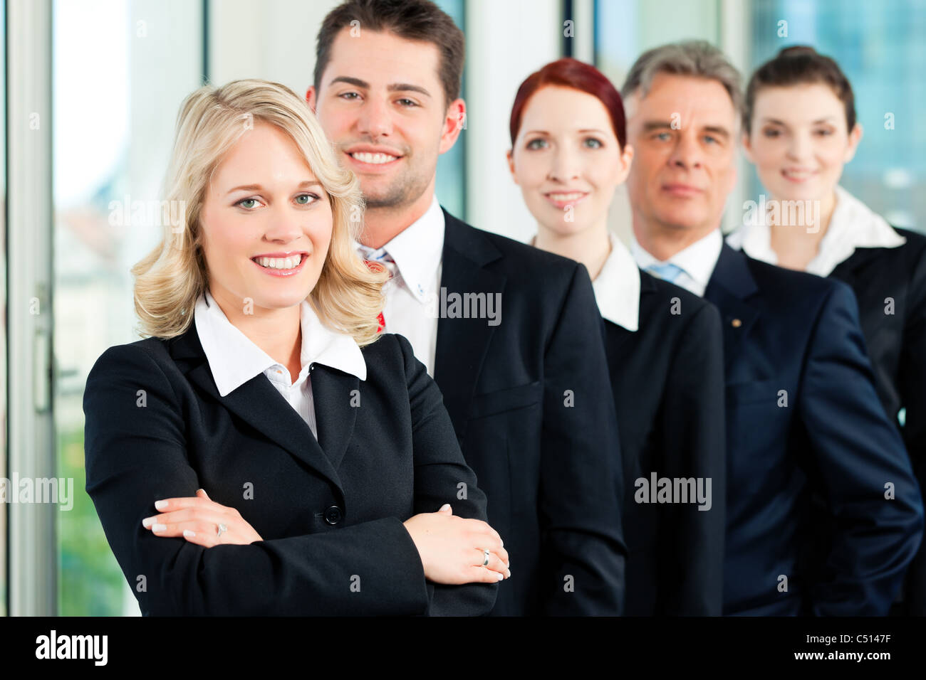 Business - team in an office; five colleagues or professionals in a row - Stock Image