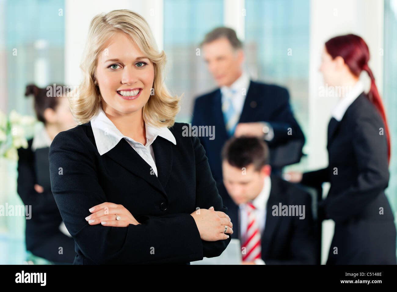 Business - meeting in an office; a colleague is looking into the camera - Stock Image