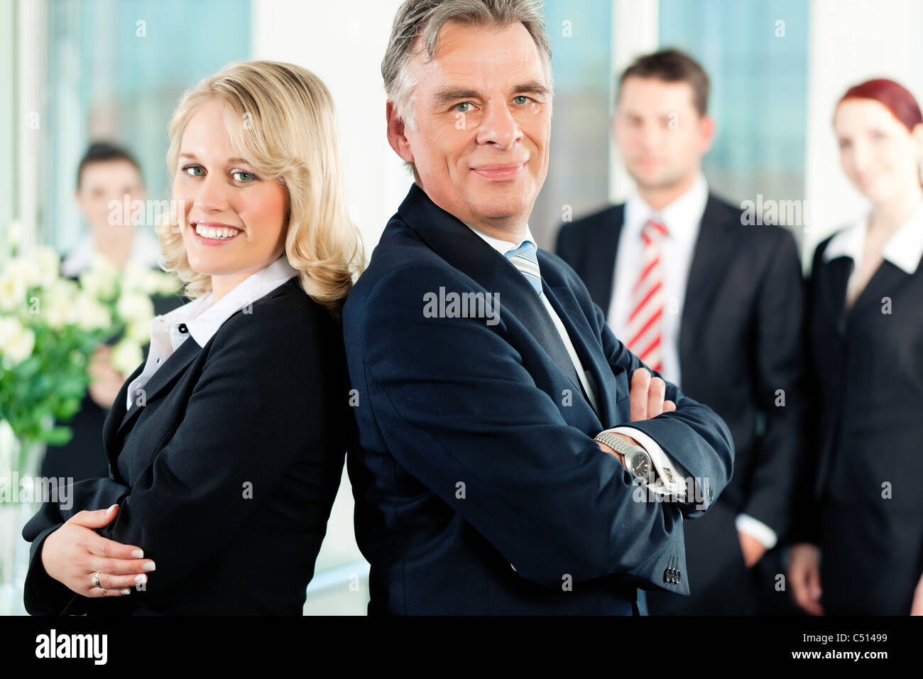 Business - team in an office; the senior executive is standing in front with his secretary - Stock Image
