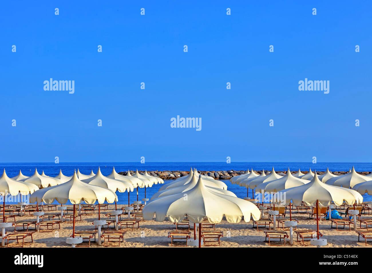 Umbrellas of the beaches on the beach of Arma di Taggia in Liguria on the Mediterranean - Stock Image
