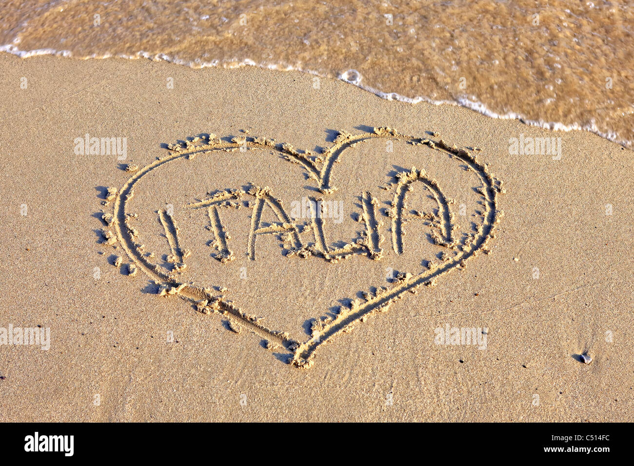 a heart in the sand beach with Scripture Italia - Stock Image