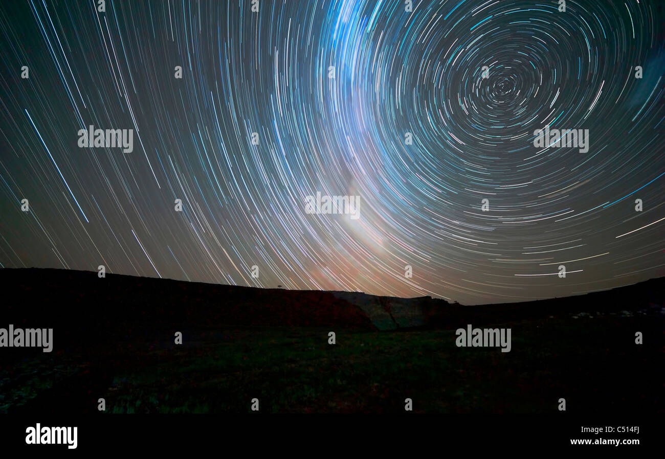 Star trails around the south celestial pole, Somuncura, Argentina. The Milky Way is also visible trailing in the - Stock Image