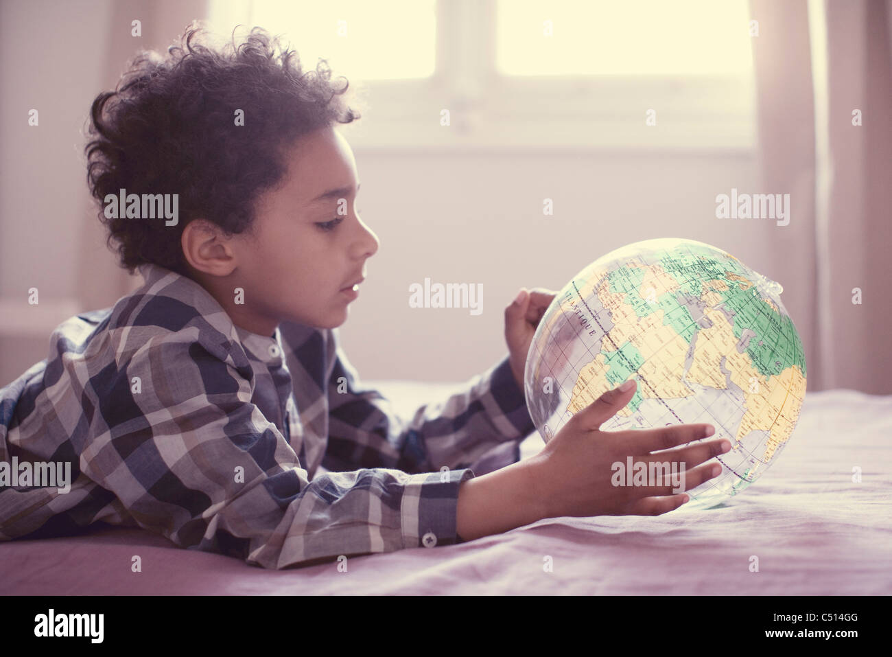Little boy looking at inflatable globe - Stock Image