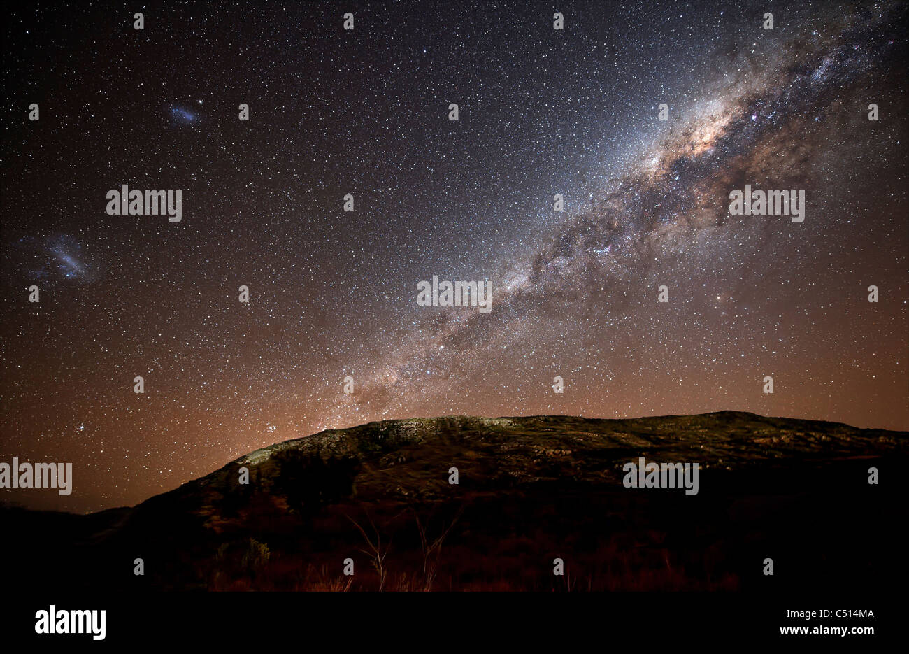 The Milky Way and its satellite galaxies the Magellanic Clouds rising above the hills of Azul, Argentina. - Stock Image