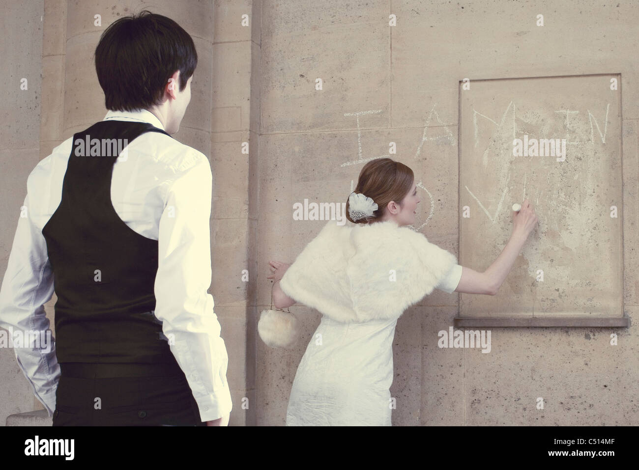 Bride writing 'I AM IN LOVE' on wall, groom watching - Stock Image