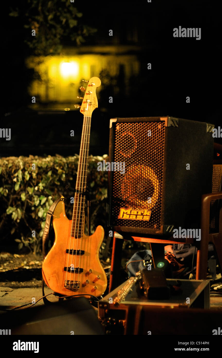 Bass guitar and amplifier set up outdoors for nighttime performance - Stock Image