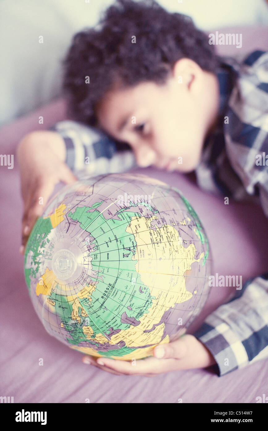 Little boy contemplating at inflatable globe - Stock Photo