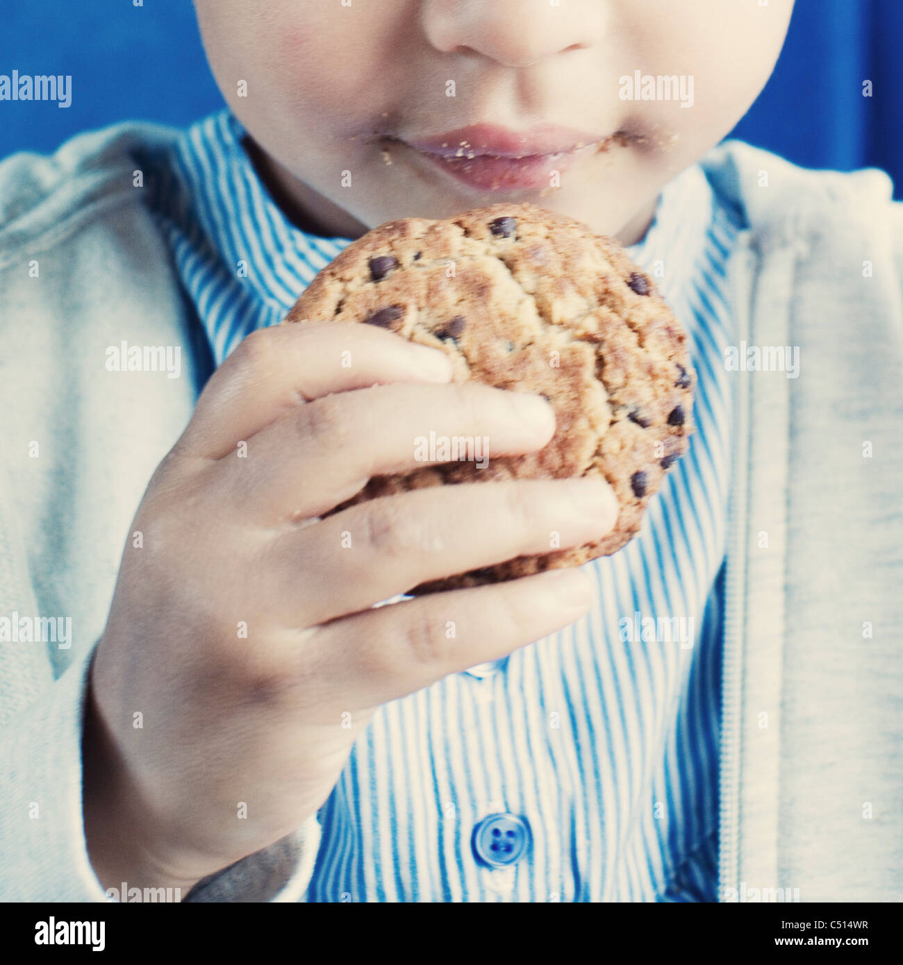 Little girl holding cookie, mid-section - Stock Image