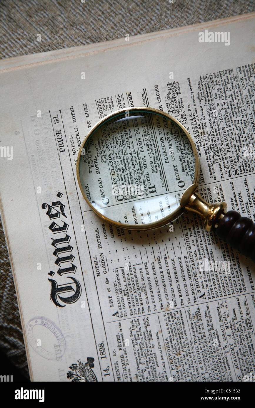 Magnifying glass over old newspaper - Stock Image