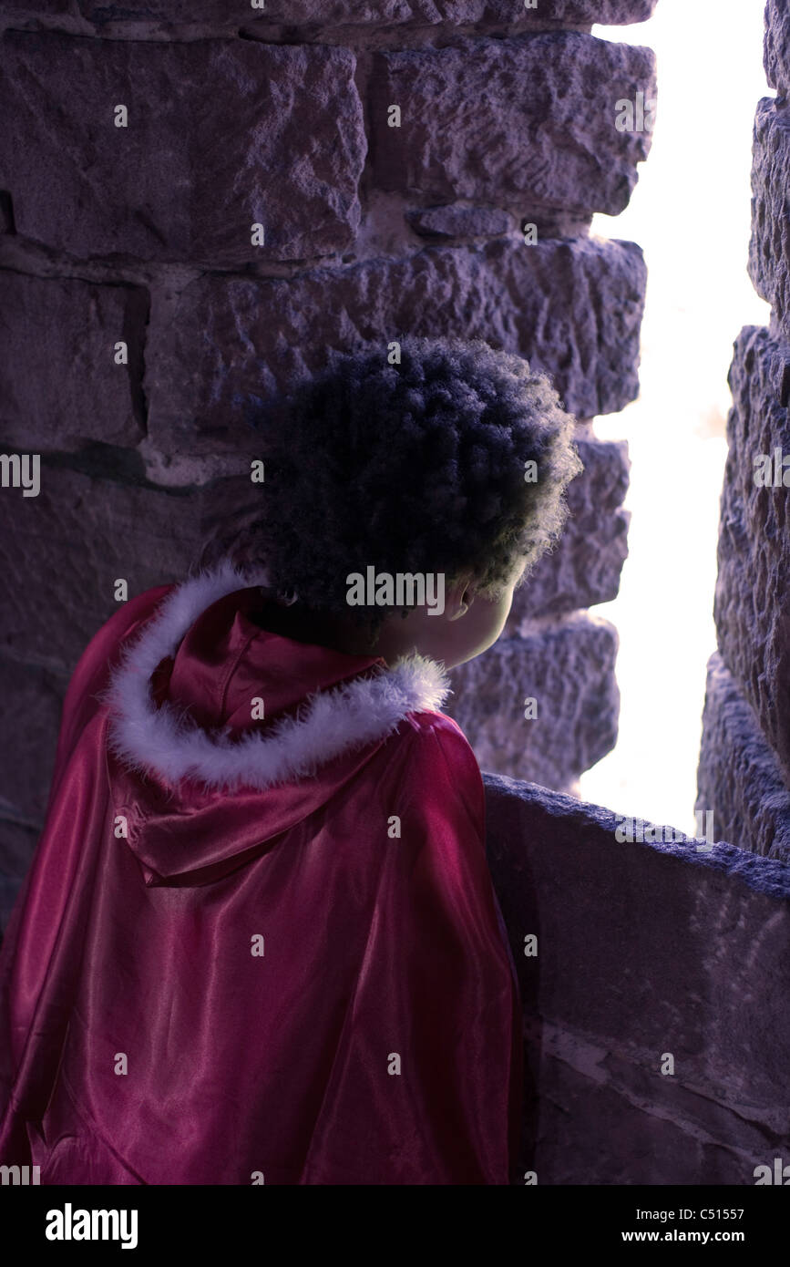 Little girl wearing cape looking out from stone building, rear view - Stock Image