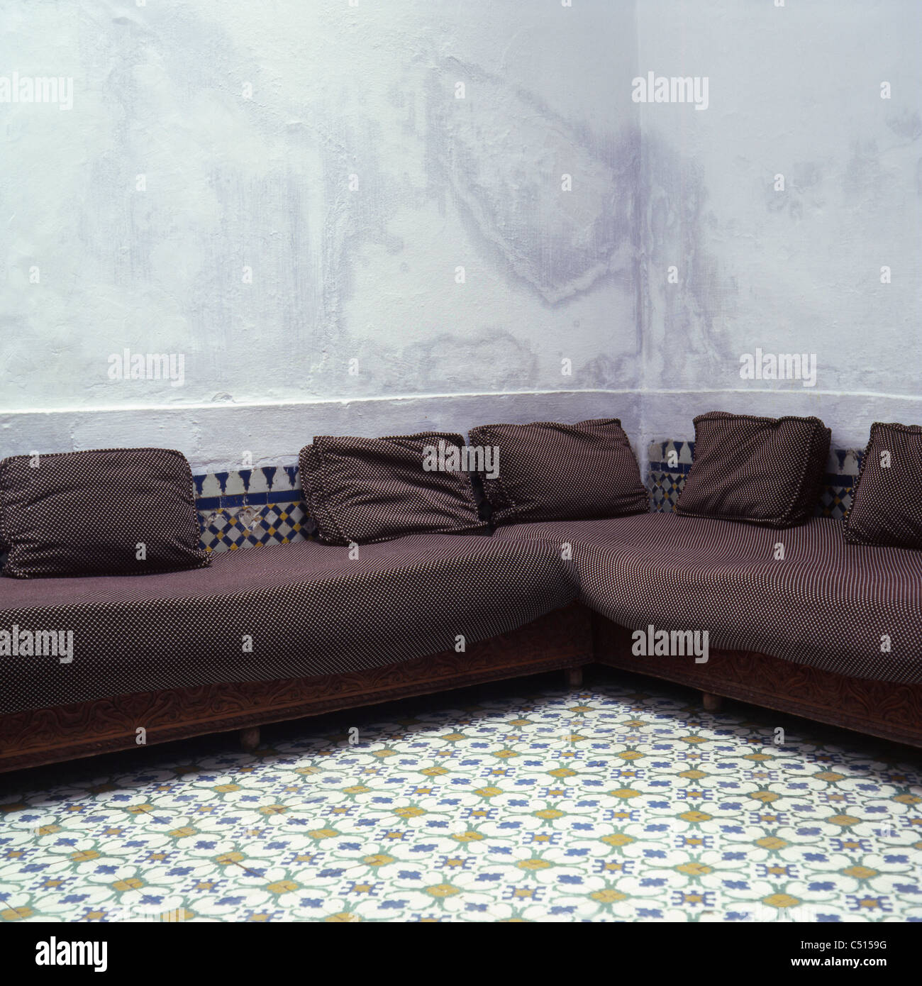 Couch in corner of room with tiled floor Stock Photo