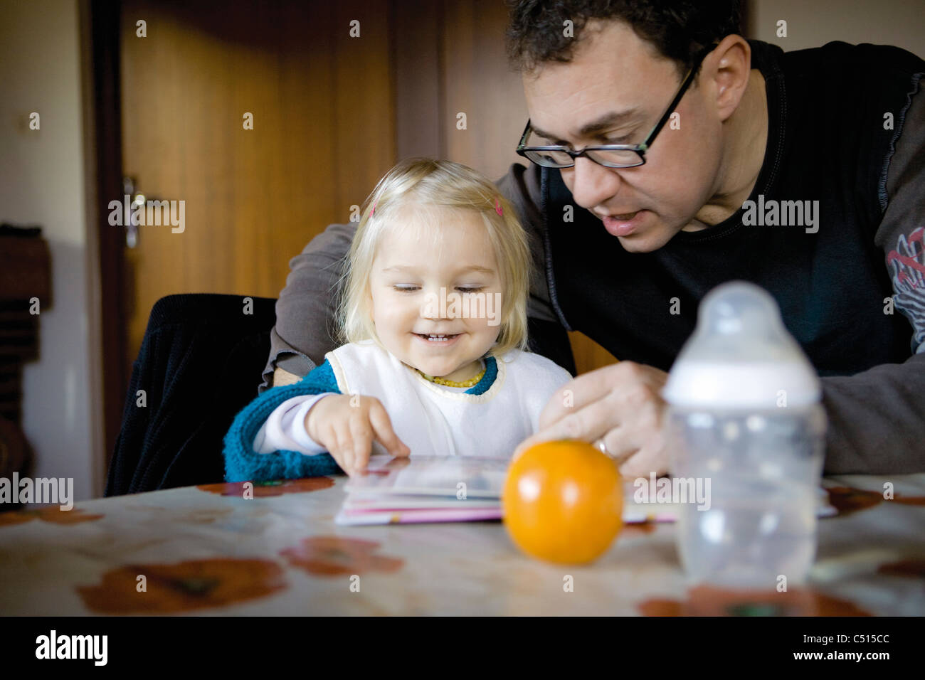 Father reading story to baby girl - Stock Image