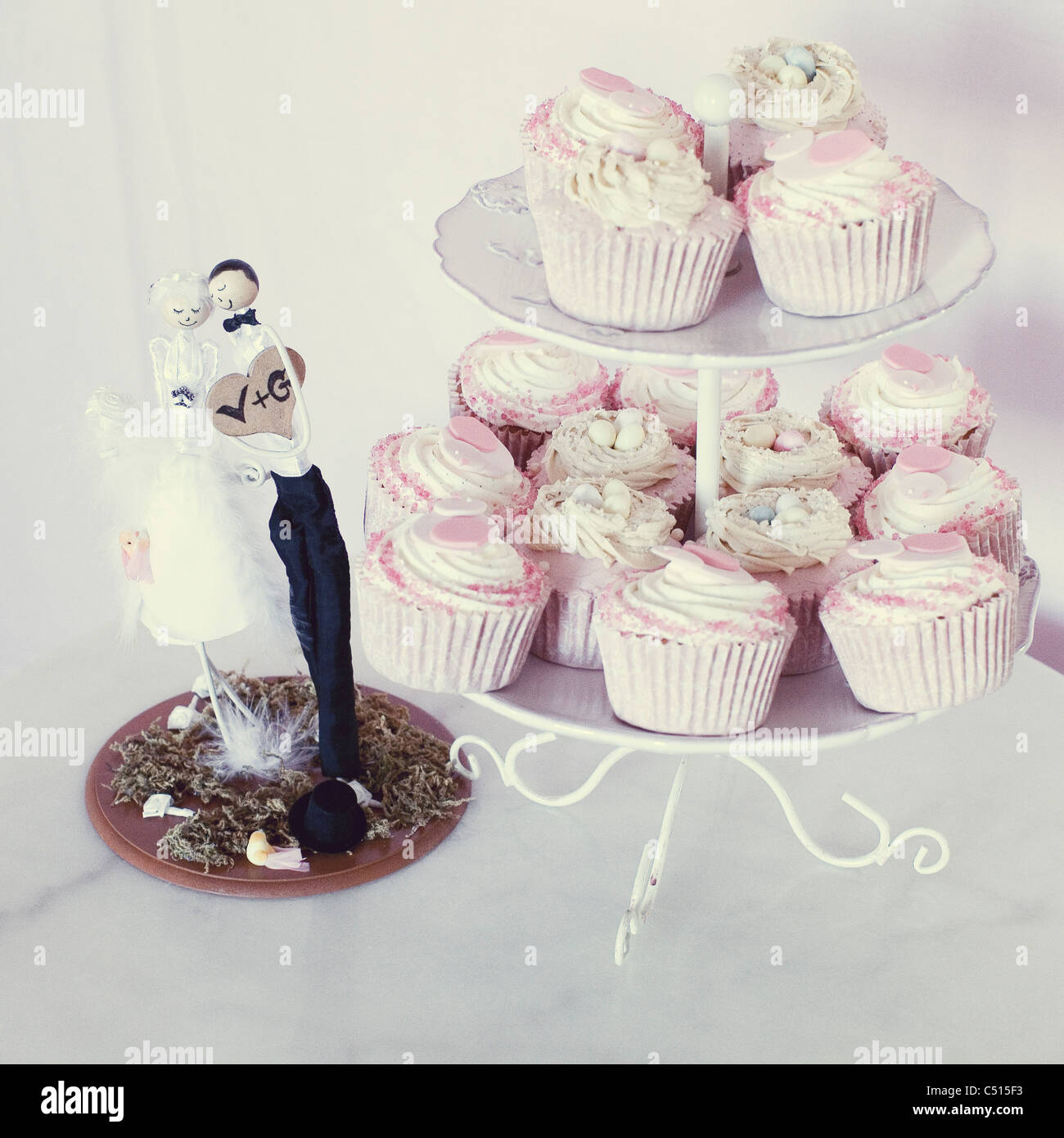 Wedding cupcakes on cake stand next to bride and groom cake topper ...