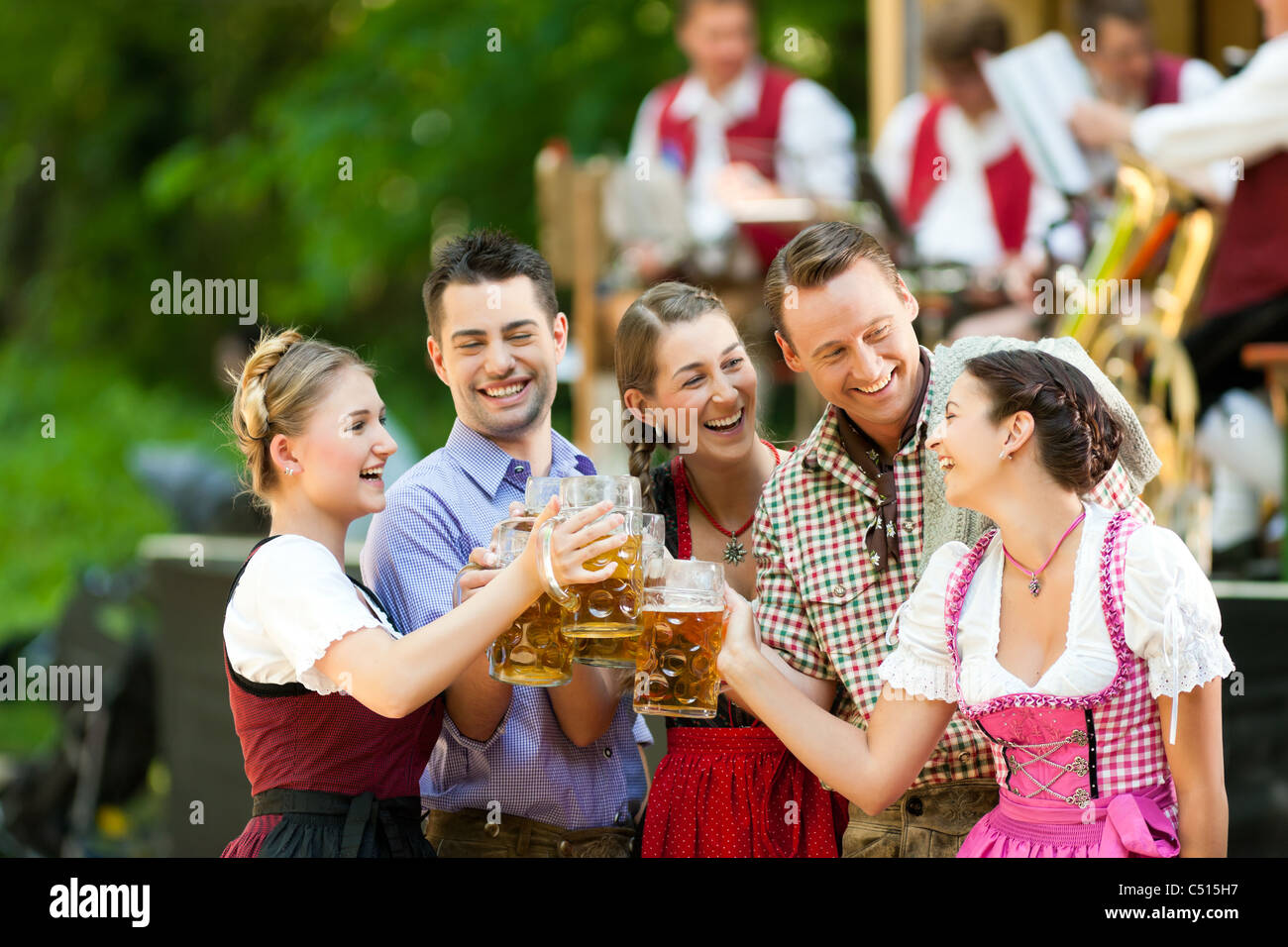 In Beer garden in Bavaria, Germany - friends in Tracht, Dirndl and Lederhosen and Dirndl standing in front of band - Stock Image