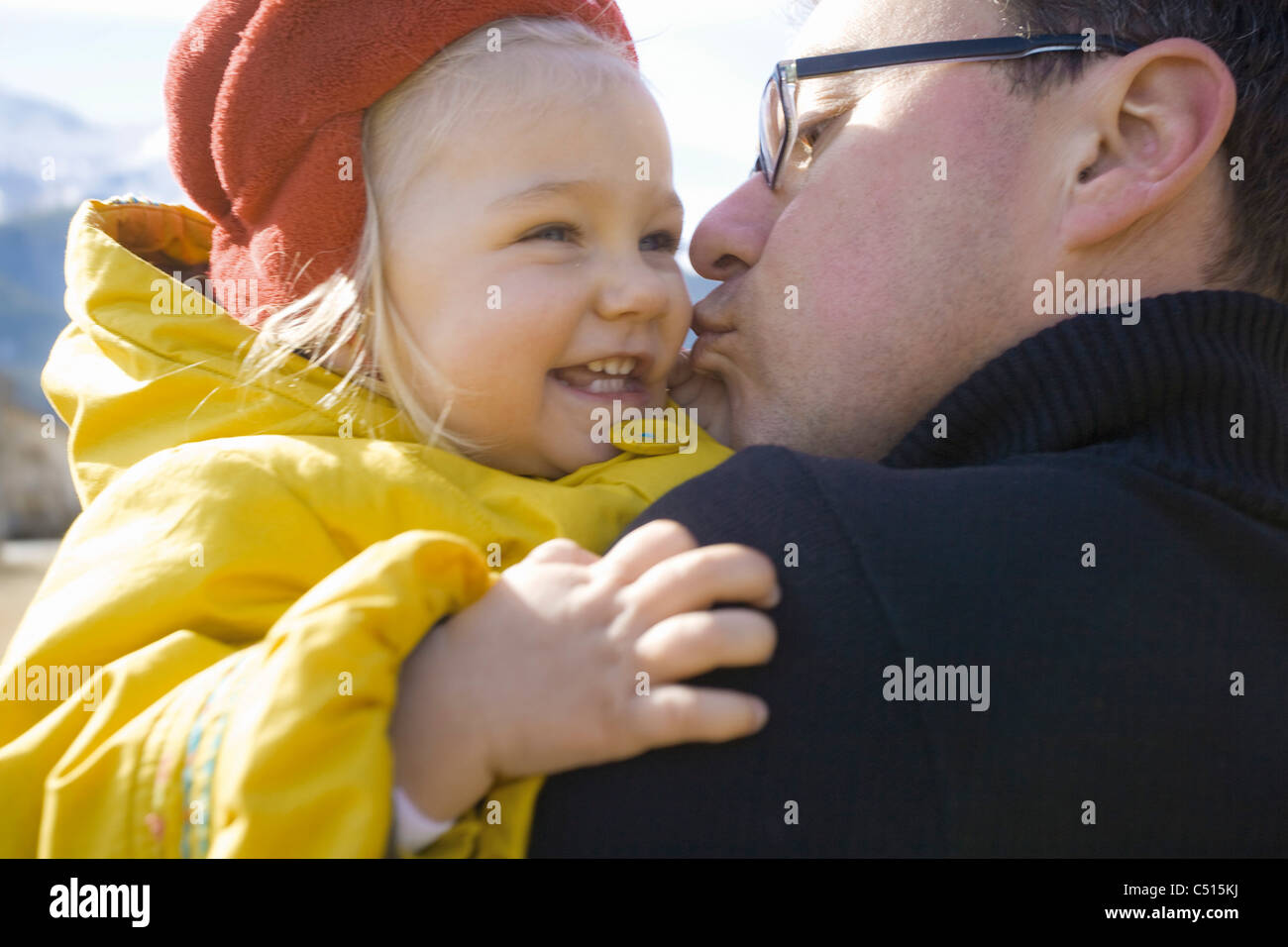 Father kissing baby girl on the cheek - Stock Image