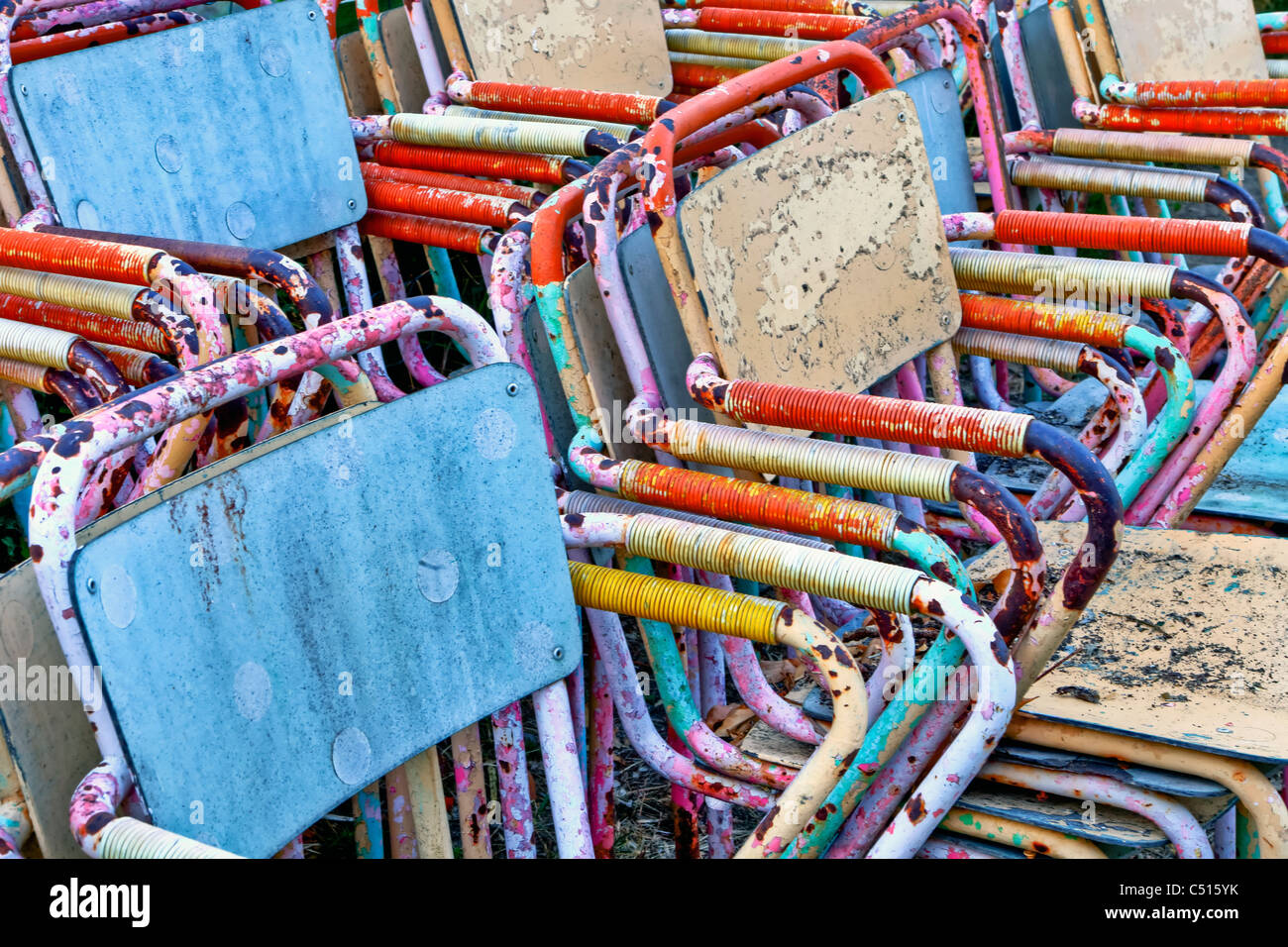 Colourful and rusty old chairs stacked - Stock Image