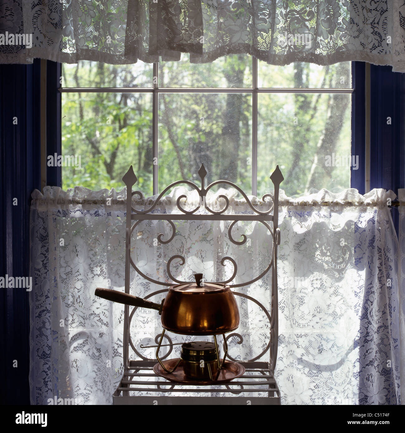 Old-fashioned pan on shelf in front of window - Stock Image