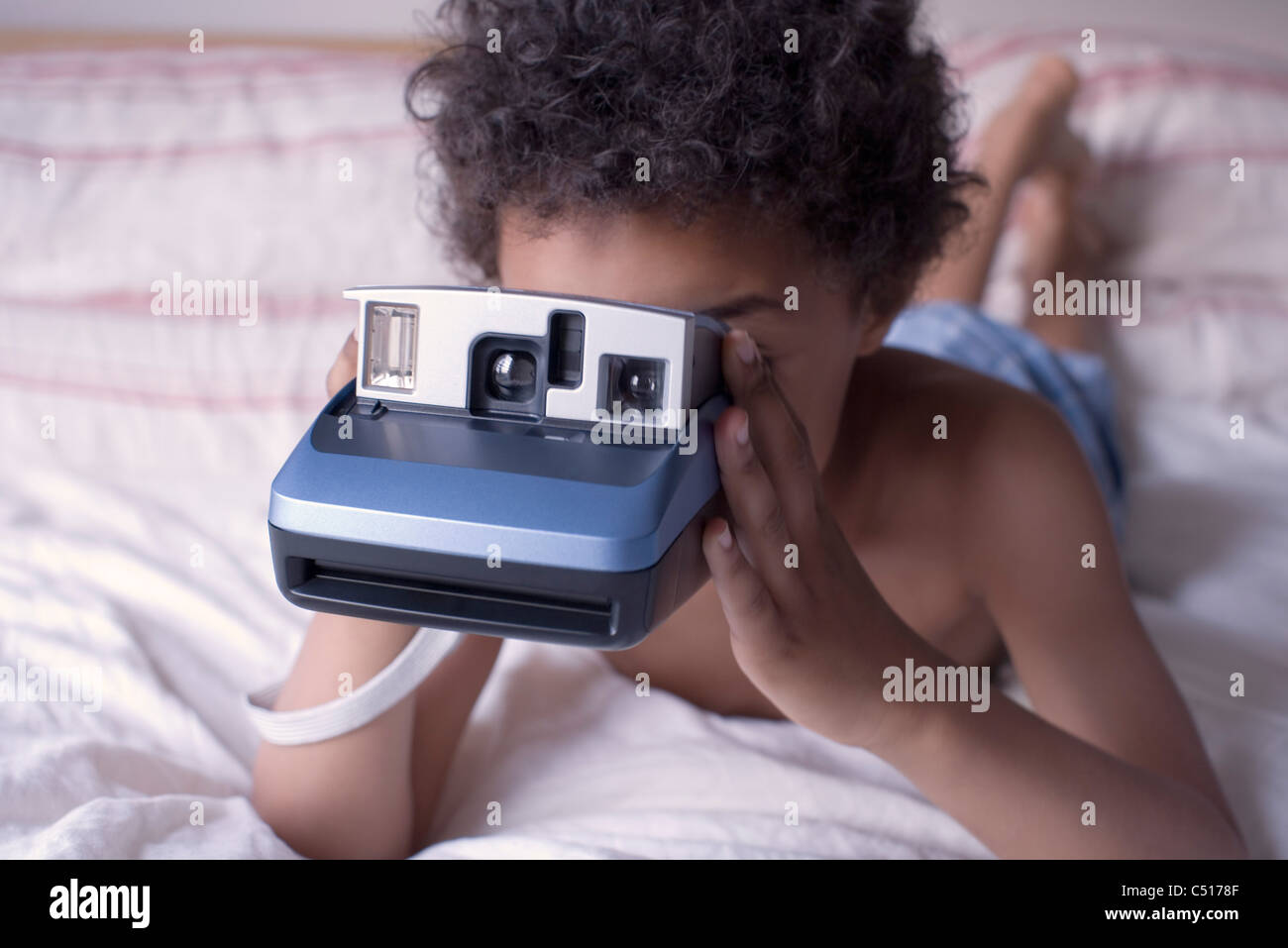 Liitle boy holding instant camera - Stock Image