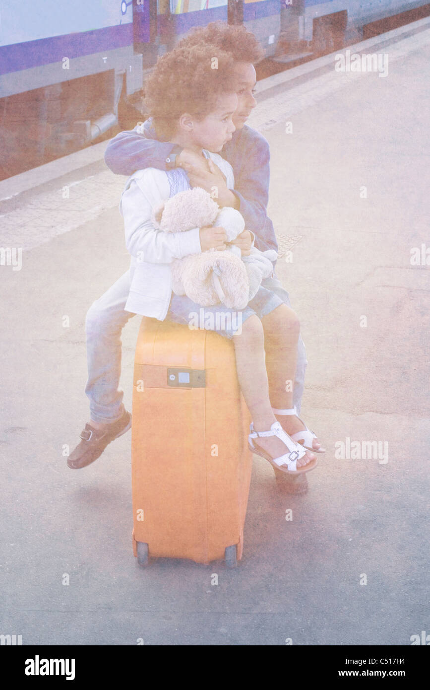 Brother and sister sitting together on suitcase waiting in train station Stock Photo