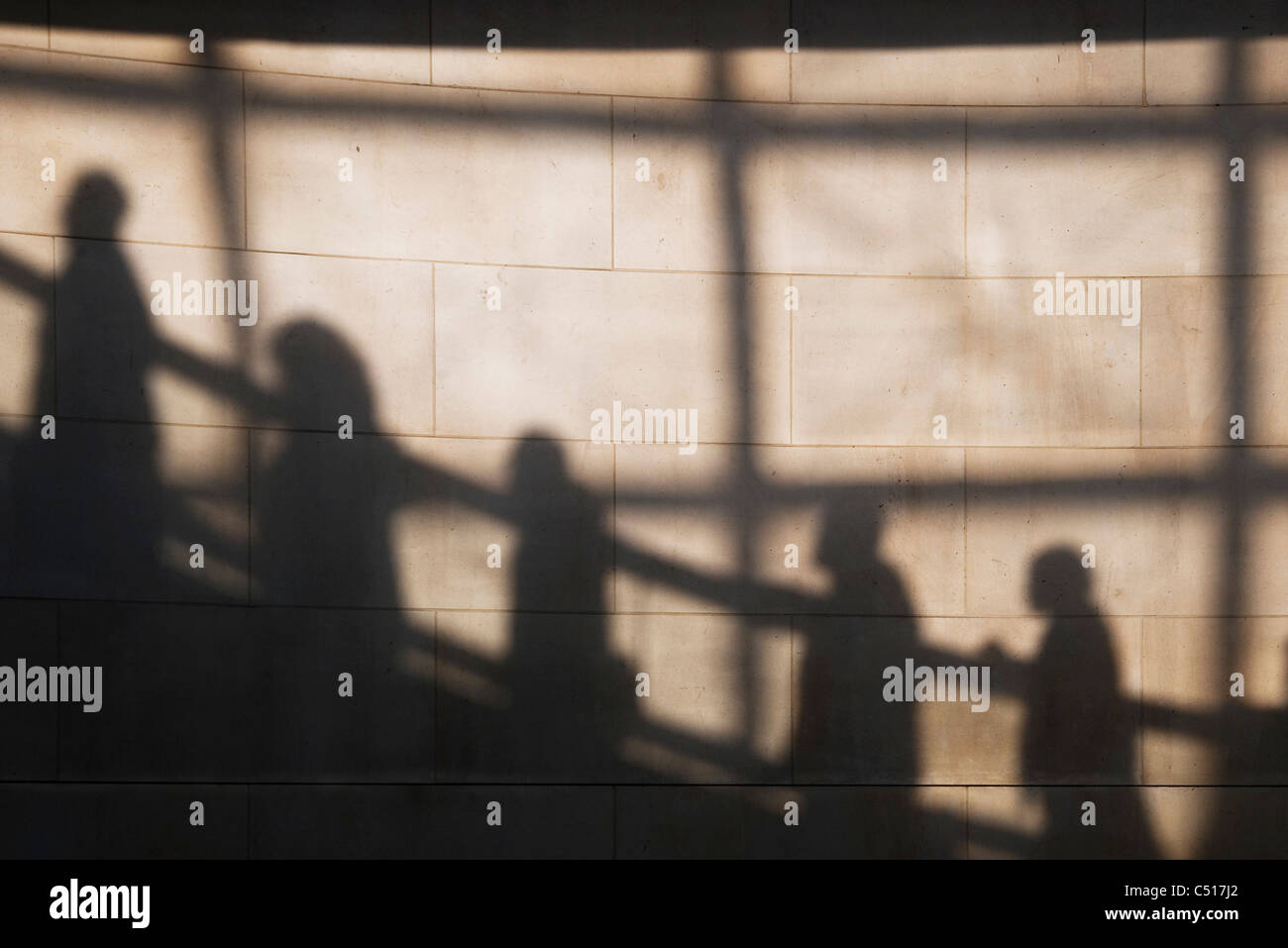 Shadow on wall of people riding escalator - Stock Image