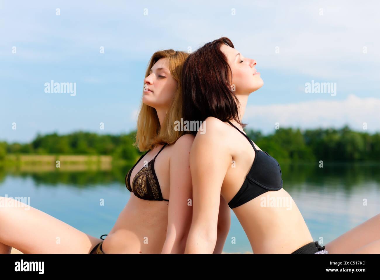 Two happy women having fun in summer at lake; they wearing swimwear - Stock Image