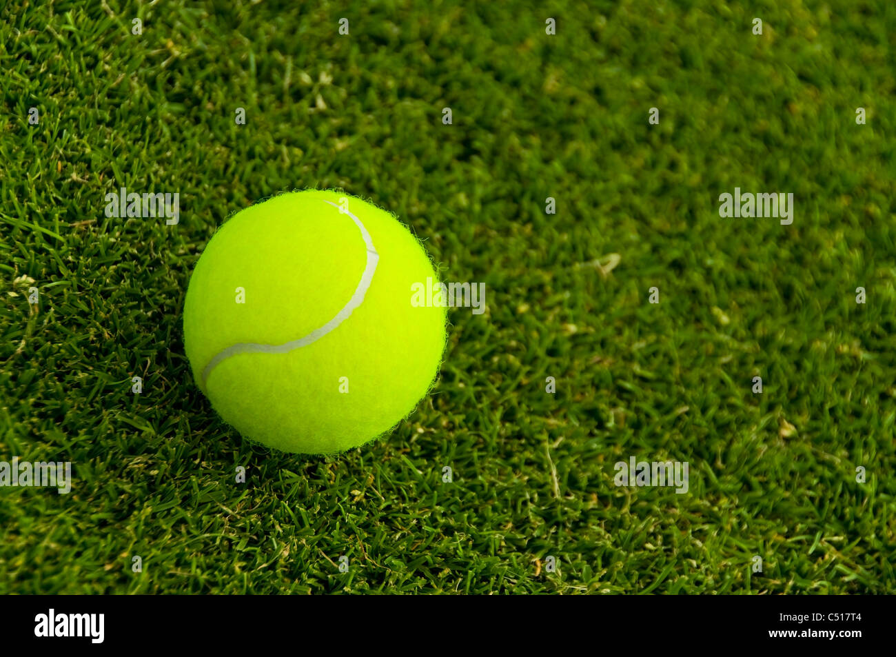 A tennis ball on a lawn court - Stock Image