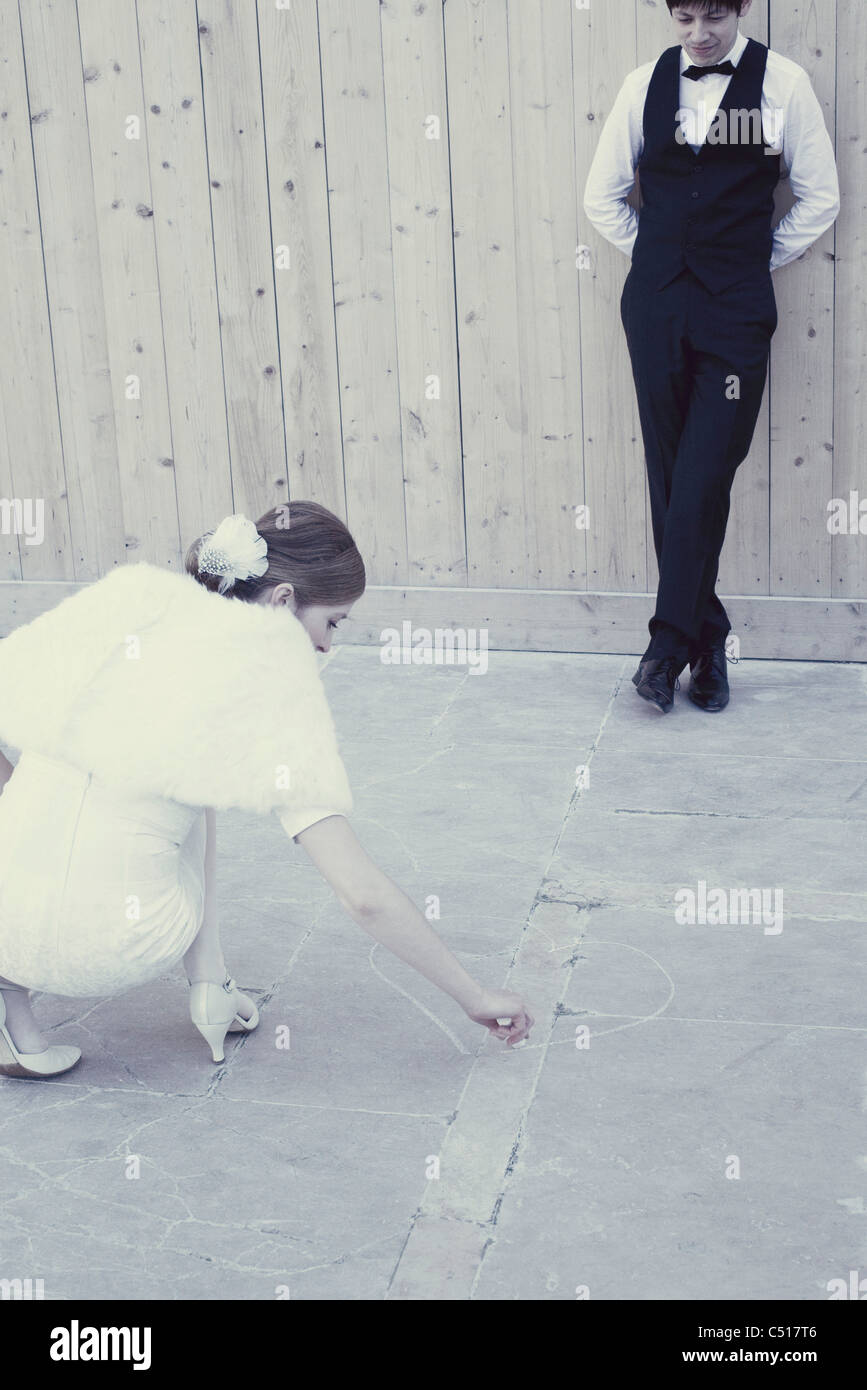 Woman drawing heart on the ground, man watching - Stock Image