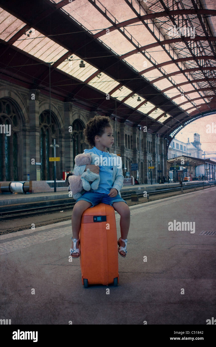 Little girl sitting on suitcase waiting in train station Stock Photo
