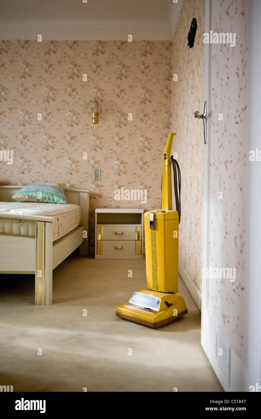 Vacuum cleaner in emptied bedroom Stock Photo