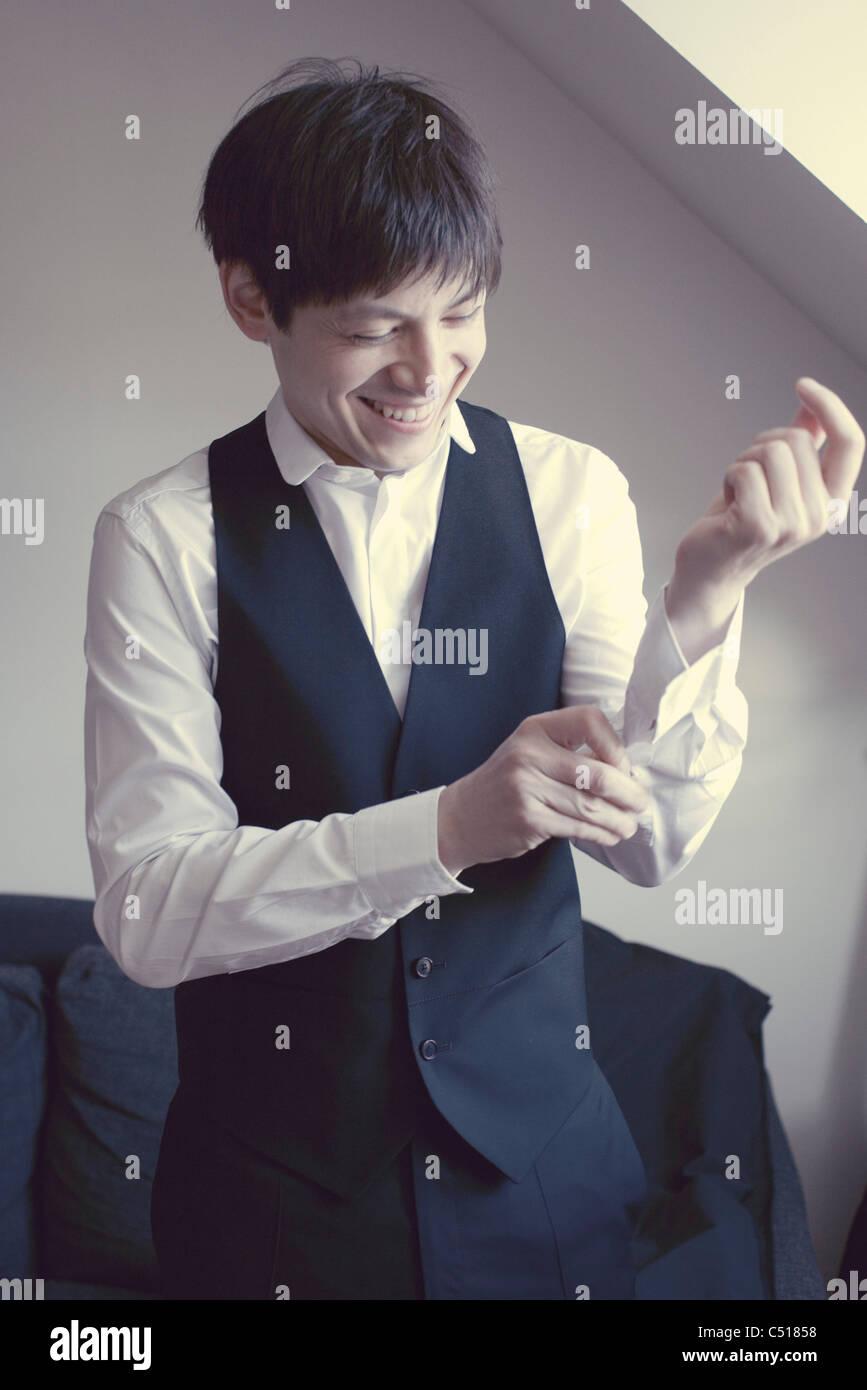 Man buttoning shirt cuff - Stock Image