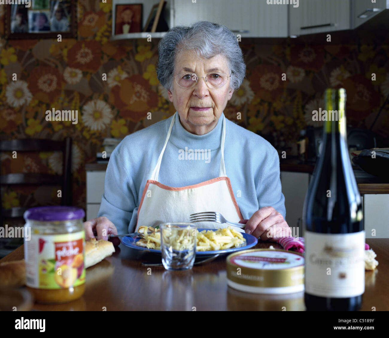 Senior woman eating at table, portrait - Stock Image