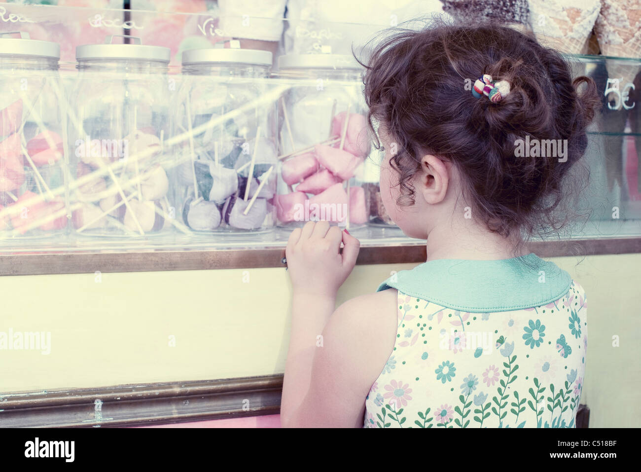 Little girl looking at jars of colorful marshmallows, rear view - Stock Image