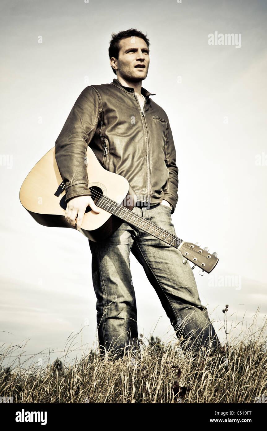 Man standing with a guitar in a meadow - Mann mit Gitarre auf einer Wiese - Stock Image