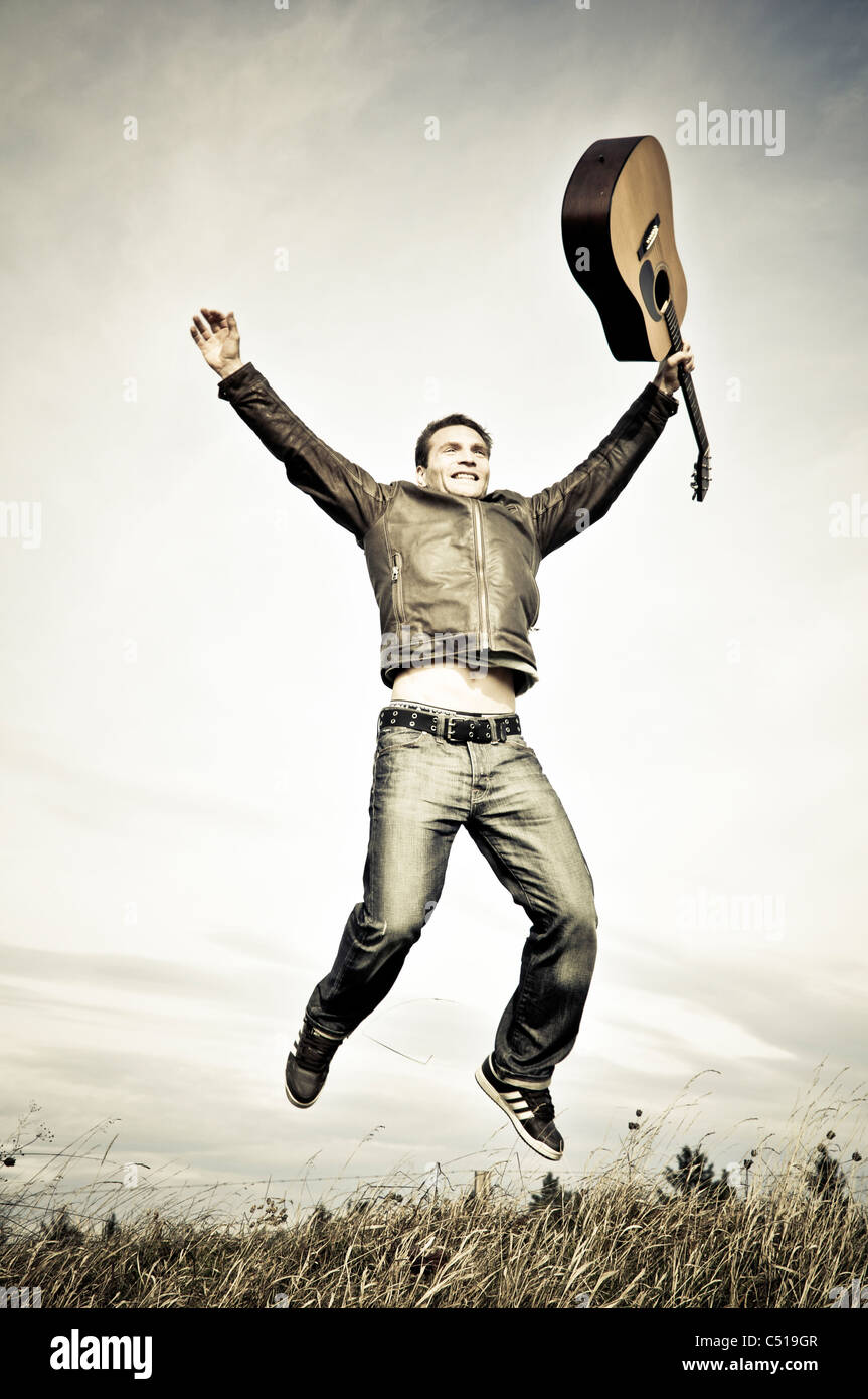 Man jumping with a guitar in his hand - Stock Image